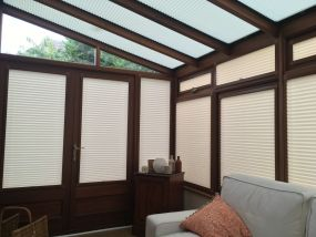 Cream coloured window and door blinds in wooden conservatory - Conservatory Roof Blinds